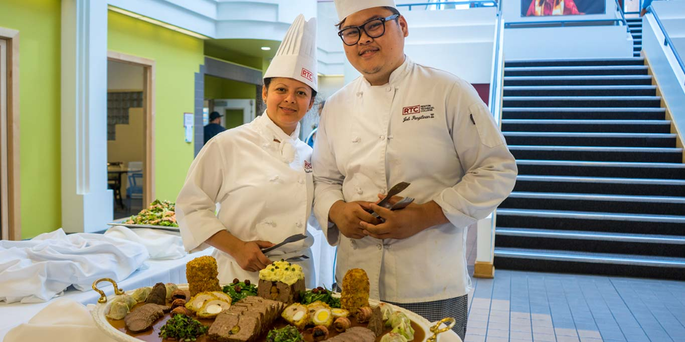 Two RTC culinary students with a platter of food