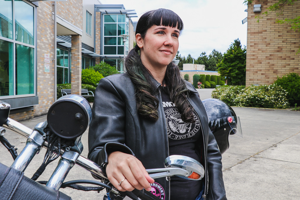 Rachel Houghton sitting on a parked motorcycle looking at something in the distance