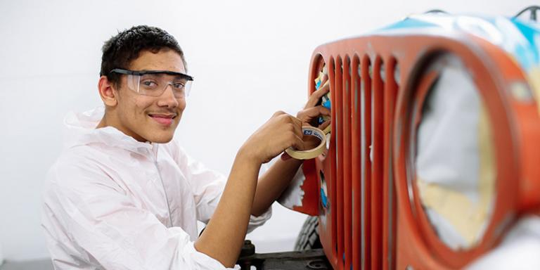 An autobody student taping a car